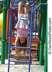 A 9 year old girl upside down on monkey bars.
