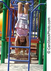 Upside-down girl on monkey bars - A 9 year old girl upside...