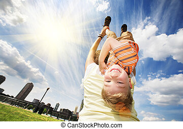Upside down - Happy young boy hanging upside down on mother'...