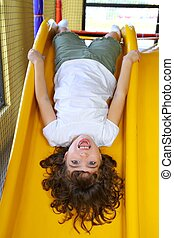 upside down little girl on playground slide laughing happy ...