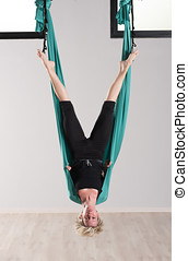 Upside down woman doing aerial yoga head stands