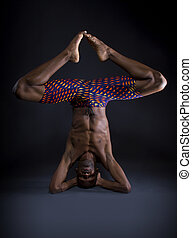 Upside Down Yoga - muscular black man doing upside down yoga...