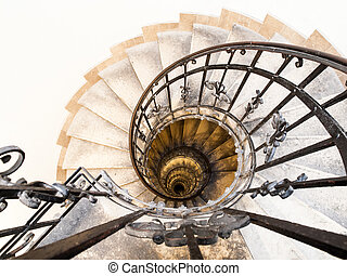 Upside view of indoor spiral winding staircase with black metal ornamental handrail