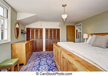 Upstairs bedroom with master wooden bed and built-in wardrobe.