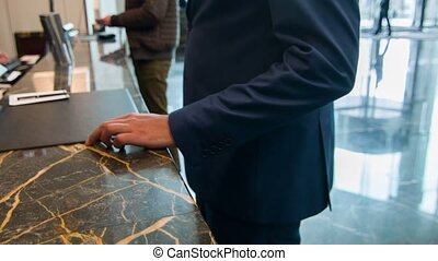 Arrival to hotel. Young businessman coming to reception desk and filling in a form while registering to get a key to a hotel room