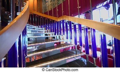Upward motion by spiral staircase in restaurant on ship...