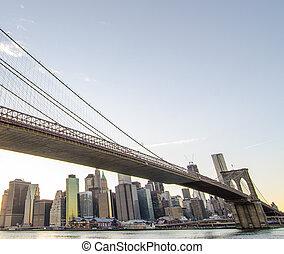 Upward view of Brooklyn Bridge at Sunset with Manhattan Skyline