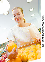 Upward view of lady holding orange in a shop
