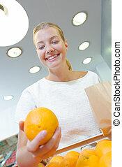 Upward view of lady holding orange