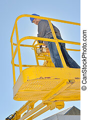 Upward view of man in cherry picker bucket