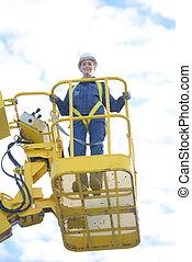 Upward view of woman in bucket of crane