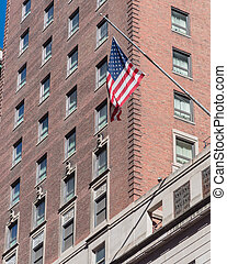 Upward view waving American flag on federal buildings in ...