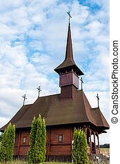 Upwards view of an old wooden church with thuja trees in front on a cloudy sky in Maramures