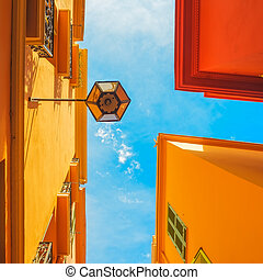 Urban abstract. Street lamp, red yellow orange house facade and
