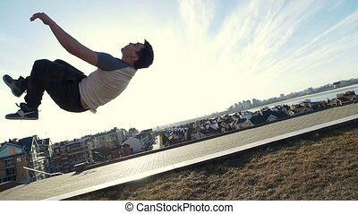 Urban acrobatics - teenager performing somersault outdoor -...