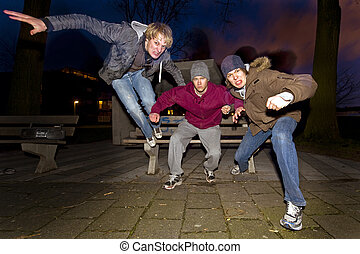 Urban aggression - Three juveniles leaping off a park bench,...