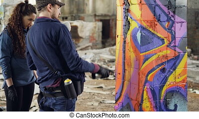 Urban artist handsome bearded man is teaching amateur...