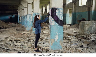 Urban artist is decorating column in abandoned warehouse...