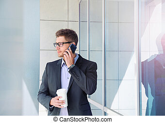 urban attractive businessman with phone device and coffee on off