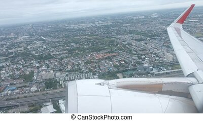 """Urban center, from window of airliner, with the plane's wing and engine"""