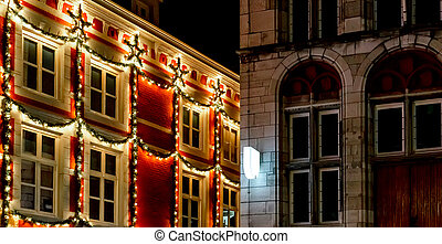 Urban Christmas facade decorations. Christmas garland lights up on window house. Festive lighting of city streets. New Year's decor. European vintage christmas