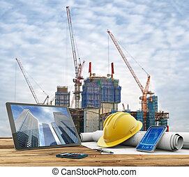 urban construction site - blueprints and safety helmet over...