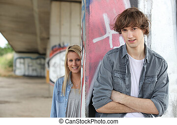 Urban couple stood by gratified wall