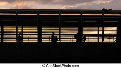 People rushing throug a station overpass, silhouettes against, sunset sky, comuting to work