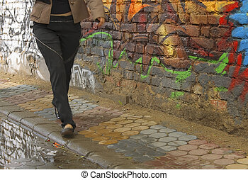 Urban culture - Girl walking by an old graffiti bricks wall...