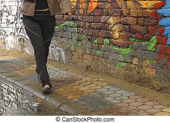 Urban culture - Girl walking by an old graffiti bricks wall...