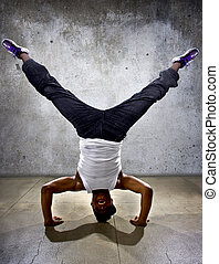 Inverted black breakdancer doing a headstand or handstand or urban yoga