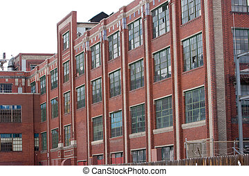 Abandoned old manufacturing plant - broken windows and boarded up.