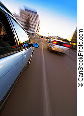 Urban Driving - A car passing another vehicle in an urban...