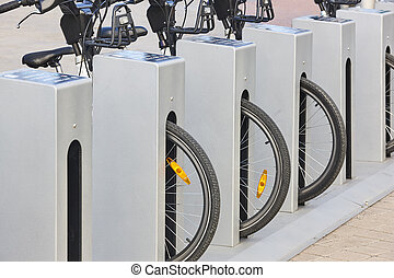 Urban electric bikes charging batteries in the city. ...