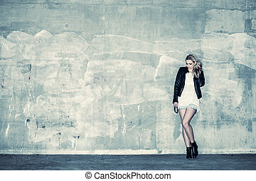 Beautiful urban girl leans against a concrete wall, cross processed image