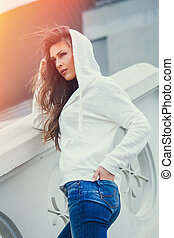 urban girl in blue jeans and white sweater with hood summer day in city