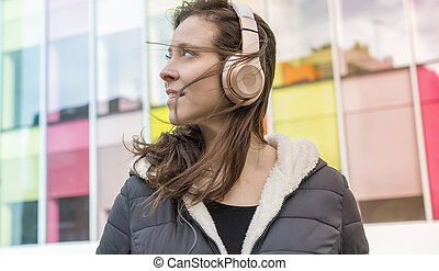 urban, girl in the street listening to music with headphones on her head, she wears a long hair to the wind and winter jacket