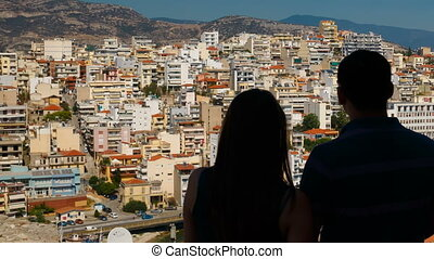 A silhouetted millennial young couple observing the urban jungle in the coastal town of Kavala, northern Greece. Kavala is the main seaport of eastern Macedonia