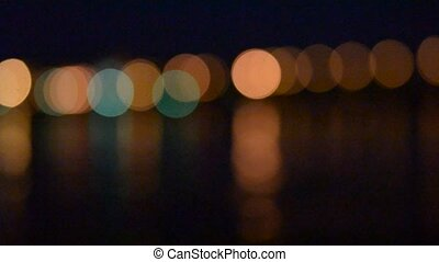 Urban landscape with city lights reflected in water in the evening at night