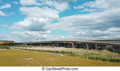 Urban landscape with overpass elevated bridge above city river in industrial zone of Kaliningrad, Russia at daytime. Static shot rendered in 4K