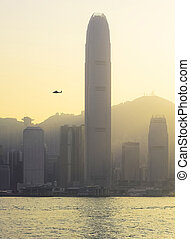 Urban life - Helicopter flying in Hong Kong sky at sunset
