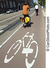 biking in Amsterdam - urban lifestyle: couple biking in...