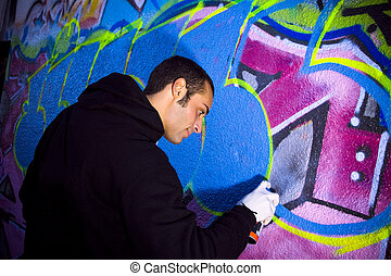urban lifestyle: young man painting on a wall