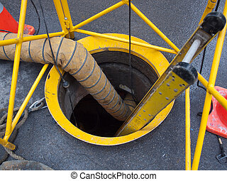 Urban Maintenance - Open manhole with ladder and barrier and...