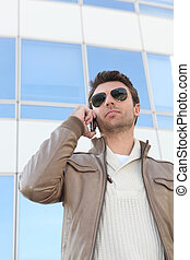 Urban man in aviators with a mobile phone