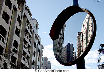A mirror reflects several buildings.