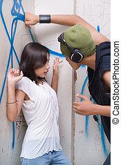 Urban mugger intimidating girl - Young tough Hispanic grunge...
