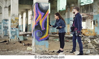 Urban painter is explaining to attractive young woman how to...