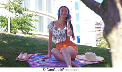 Urban Picnic - Young pretty woman listening to music in her headphones and making dance moves