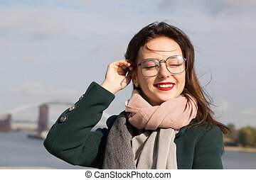 Urban portrait of beautiful brunette girl posing at the city, wearing glasses, coat and scarf